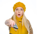 Surprised girl in autumn clothes using tv remote control