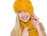 Smiling girl in autumn clothes pulling hat over head