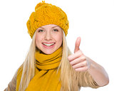 Happy girl in autumn clothes showing thumbs up