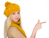 Girl in autumn clothes pointing on copy space