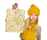 Happy girl in autumn clothes showing shopping bag