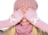 Portrait of happy girl in winter clothes covering eyes with hand