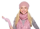 Smiling girl in winter clothes presenting something on empty pal
