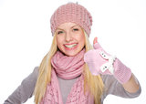 Happy girl in winter clothes showing thumbs up