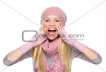 Happy girl in winter clothes shouting through megaphone shaped h
