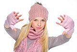 Girl in winter clothes stretching hands into camera