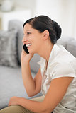 Smiling young woman sitting on couch and talking cell phone