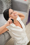 Happy young woman sitting on floor and talking mobile phone
