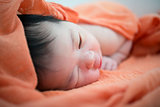 Newborn Asian baby girl on bed