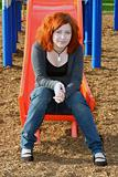 Teen Sitting On Sliding Board