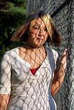 Young Blond Woman Covered By Fence Shadows
