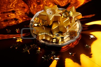 Christmas candles-stars on the shiny gold background