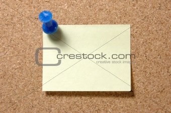 Post-it note with pushpin on corkboard