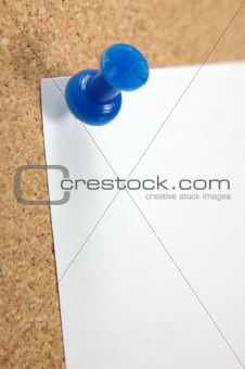 Close up of pushpin with blank note on corkboard