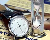 Hourglass and watch on the book on management of time