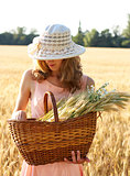 Beautiful woman in the hat with basket full of ripe ears