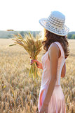 Young girl in the hat and pink dress holding wheat ears in her hand