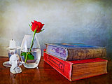 antiques books, single red rose and other paraphernalia
