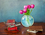 Books and glass vase with tulips