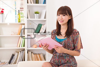 Chinese Asian girl reading a book in livingroom