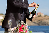 Waiter opens wedding champagne