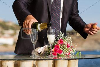 Pouring white wine into glasses