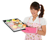 Young Asian girl baking bread and cupcakes