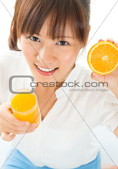 Asian girl drinking orange juice