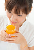 Asian female drinking orange