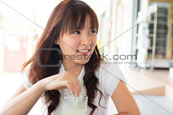 Young Asian woman enjoying drinks