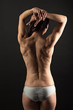Rear view of young fitness woman over black