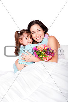 Child gives flowers to mother in bed
