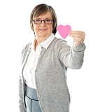 Female holding a pink paper heart