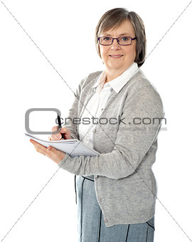 Aged woman writing on spiral notebook