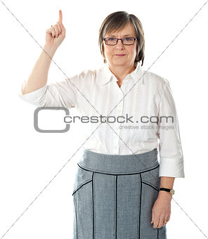 Beautiful senior business lady pointing upwards