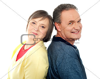 Portrait of senior couple back to back in studio