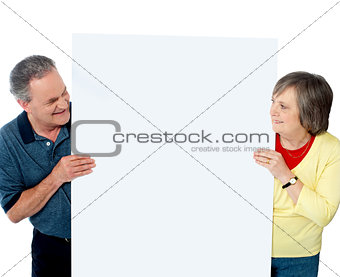 Old age couple presenting banner together