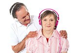 Aged couple enjoying music over white background