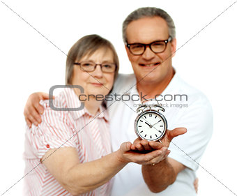 Aged couple with alarm clock on plam