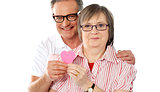 Matured smiling couple holding paper heart