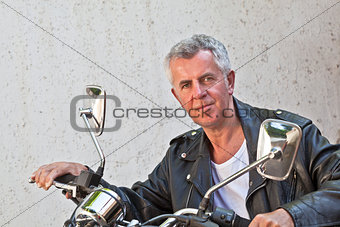 Weather beaten face Rider sat on a Motorcycle