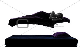 woman sleeping in levitation on bed silhouette