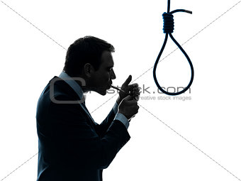 man smoking cigarette in front of  hangman noose silhouette