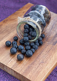 Blueberries poured from a glass jar on a wooden board on a purple background