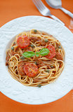 Spaghetti with tuna and tomatoes sauce on orange background