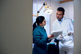 Dentist and assistant checking documents in dental studio