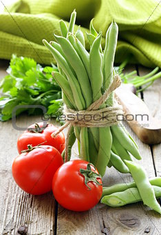 green peas  and tomatoes  on a wooden table, rustic style