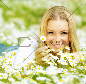 Beautiful girl enjoying daisy field