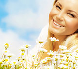 Beautiful woman enjoying daisy field and blue sky