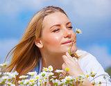 Cute female enjoying daisy smell
